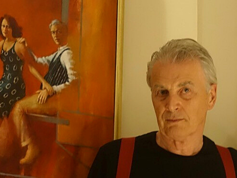 Ronnie Ireland, wearing a black t-shirt, standing in front of his painting which depict a man and a woman.