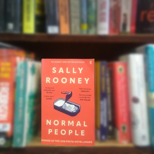 Shows based on books: front cover of Normal People, red and showing illustration of couple embracing, sitting on Library shelf.
