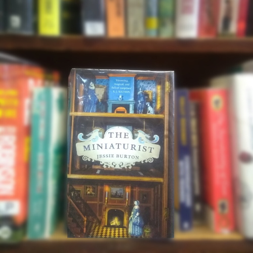 Shows based on books: front cover of the Miniaturist, showing illustrations of figures in grand interior.