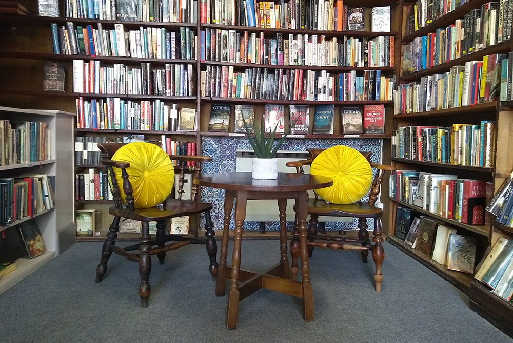 Two wooden chairs with yellow cushions and a small round table