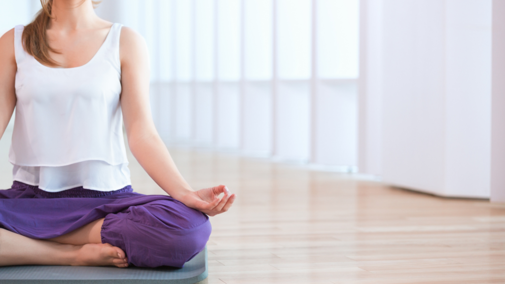 Figure wearing a white top and purple trousers, sitting on the floor in a cross legged position meditating.