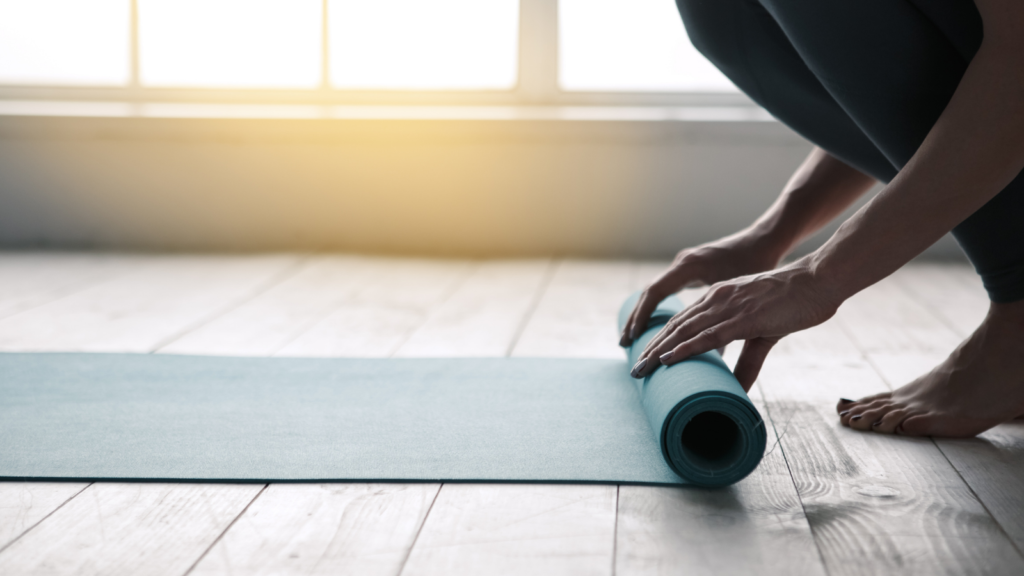 Figure crouched down on the floor, rolling a blue yoga mat out in front of them.