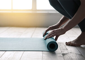 Figure crouched down onto the floor rolling out their yoga mat.